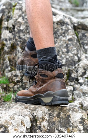 Walking on the rocks of a mountain trail with hiking boots