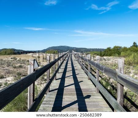 Walking on Wooden Walkway in the Sand Dunes, Portugal - stock photo