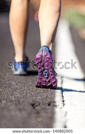 Walking or running legs on asphalt road, adventure and exercising in summer nature. Female hiker or runner foot and sport shoes doing workout outdoors. - stock photo