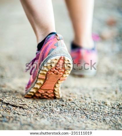 Walking or running legs on trail, adventure and exercising in mountains nature, dirt road - stock photo