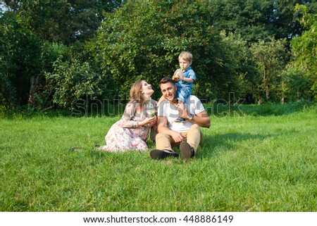 walking outdoors. Husband, pregnant wife and their son. the concept of a healthy family