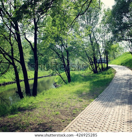 Walking path near the river. Morning run route. Paved walking path along the river. Aged photo. Early spring. Outdoors pavement path along a river. Park in a sunny day. Green trees near river. - stock photo