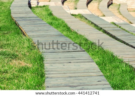 Walking paths from wooden boards among green grass. Toned - stock photo