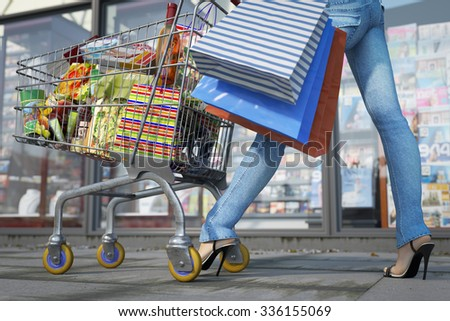 Walking shopping woman holding bag and shopping trolley close up sale concept - stock photo