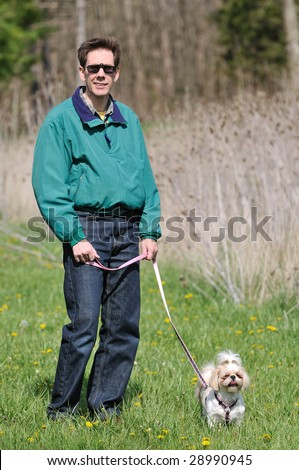 Walking the dog - a man and his dog out in the countryside on a spring day getting some exercise.