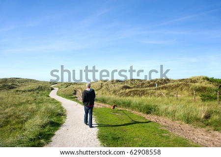Walking the dog in coast landscape with sand dunes at Ameland - stock photo