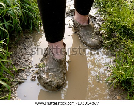 walking through the rain puddle in the muddy rubbers - stock photo