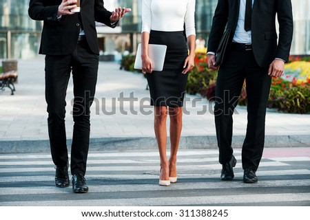 Walking to success. Cropped image of three business people crossing the street