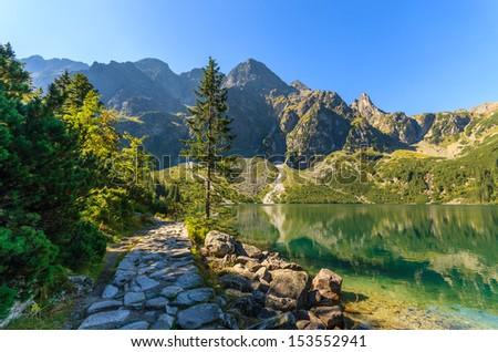 Walking trail and view of green water mountain lake Morskie Oko, Tatra Mountains, Poland - stock photo
