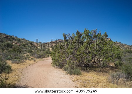 Walking trail leads into the low brush of southern California's Mojave desert near Santa Clarita. - stock photo