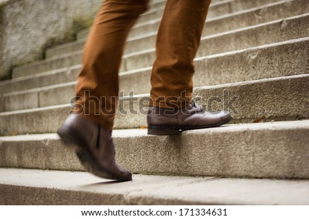 Walking upstairs: close-up view of man's leather shoes  (motion blurred image) - stock photo