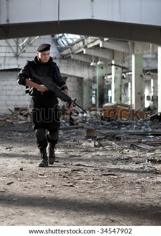 Walking warrior with the machine gun on the ruined building background. - stock photo