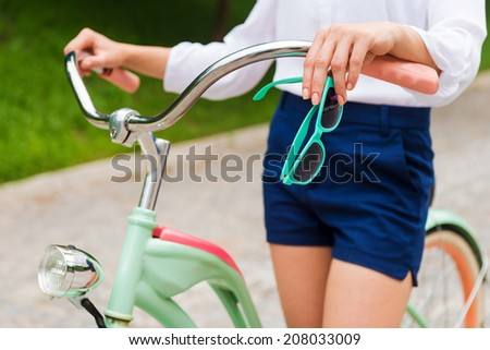 Walking with style. Close-up of young woman holding sunglasses while walking with her bicycle in park - stock photo