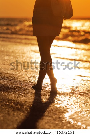Walking woman on coastline. Sunset.