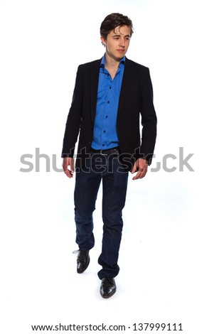 Walking young business man wearing blue jacket and jeans. Isolated on white. - stock photo