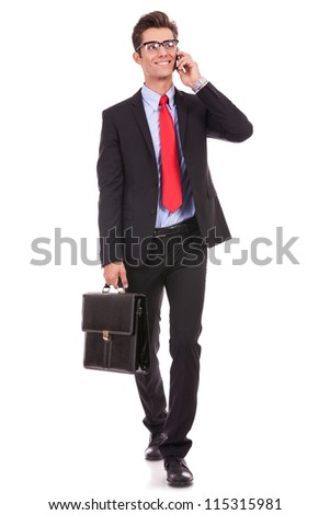 walking young business man with briefcase , looking away from the camera while speking on his smartphone, isolated on white background - stock photo
