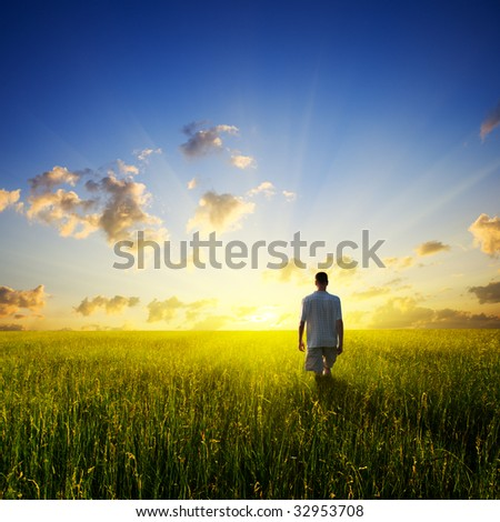 walking young man over field and sunset - stock photo