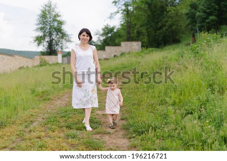 walking young woman with her daughter - stock photo