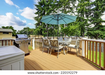 Walkout deck in brown and white trim. Patio table set with umbrella and jacuzzi - stock photo