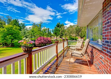 Walkout deck with sitting area decorated with flower pots. Deck overlooking front yard garden - stock photo