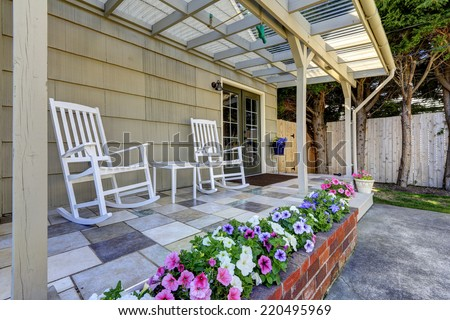 Walkout patio area with white rocking chairs and vivid blooming flowers in brick flower bed - stock photo