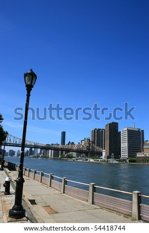 Walkway along Manhattan's Roosevelt Island.  Queensboro Bridge in the background.
