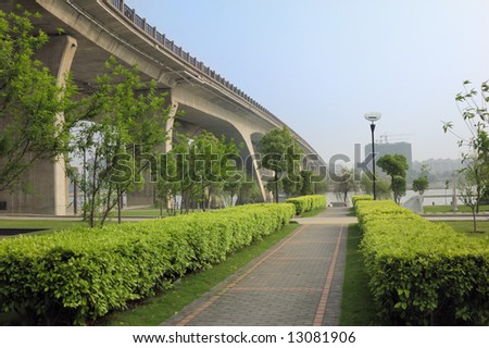 walkway and bridge,scene in a park beside a river. - stock photo