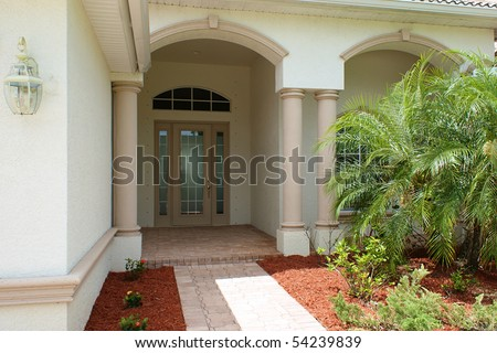 Walkway and front door to generic high end home in southwest florida with small palm tress. - stock photo