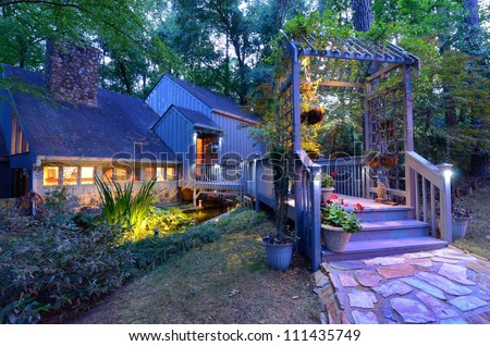 Walkway and front porch of a nice house in the woods.