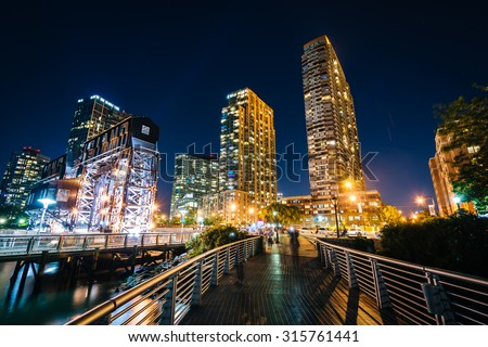 Walkway and Long Island City at night, seen from Gantry Plaza State Park, Queens, New York. - stock photo