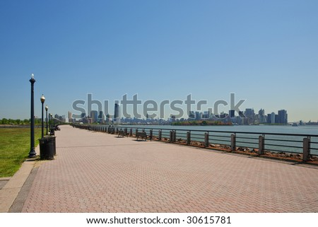 Walkway at Liberty State Park, with Jersey City, Ellis Island, and Manhattan in the background - stock photo