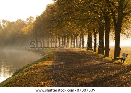 Walkway at the canal in autumn mist. - stock photo