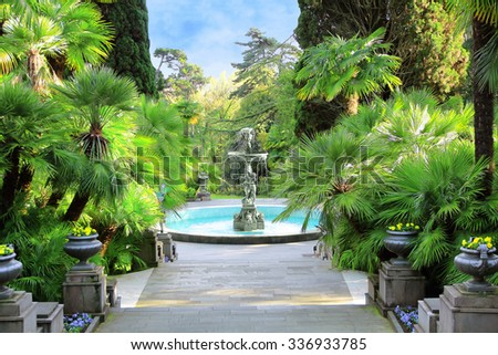 Walkway in a beautiful Park with Palms, thuyas and fountain (russia, sochi) - stock photo
