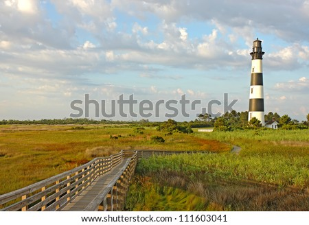 Walkway leading to the Bodie Island lighthouse over marshes of the Cape Hatteras National Seashore against white clouds and a blue morning sky - stock photo