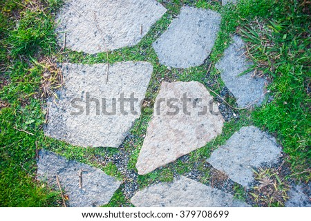Walkway made of flat large grey stones in Italian garden, top view, horizontal.