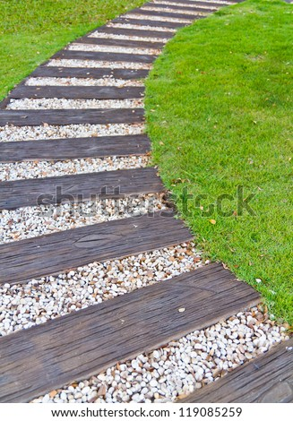 Walkway made �¢??�¢??of wood and stone on the grass - stock photo