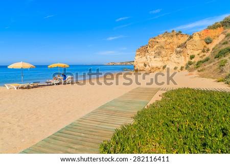 Walkway on sandy beautiful Praia da Rocha beach and two sun umbrellas in distance, Algarve region, Portugal - stock photo