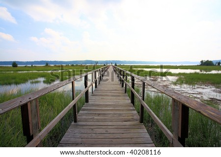 Walkway path to the edge of the bay under a big sky - stock photo