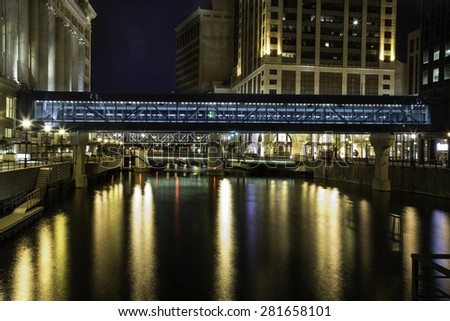Walkways spanning the Milwaukee River in downtown Milwaukee Wisconsin.  This photo was taken in the evening with long exposure to highlight the reflections of the lighting in the water. - stock photo