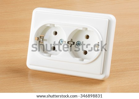 Wall AC outlet panel receptacle isolated on the wooden background - stock photo
