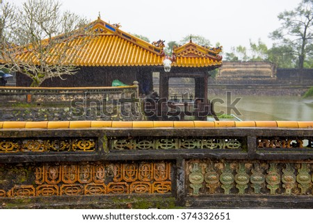 Wall and temple near the entrance to the Tu Duc Mausoleum, Vietnam.  In the rain - stock photo