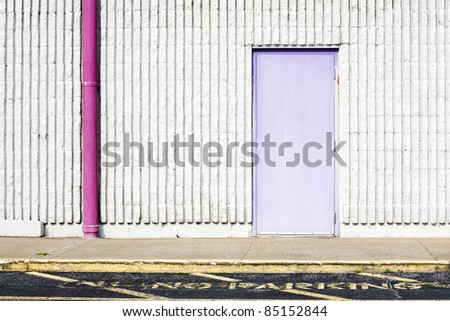 wall background with purple door, pink gutter & no parking - stock photo
