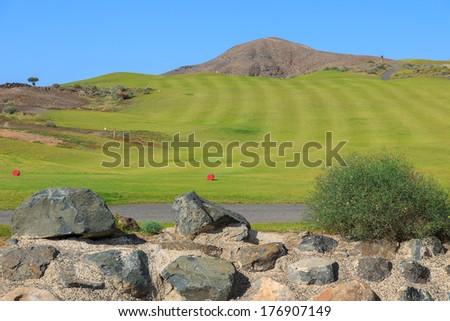 Wall built of lava stones and green lawn field of a golf course in Las Playitas town, Fuerteventura, Canary Islands, Spain  - stock photo