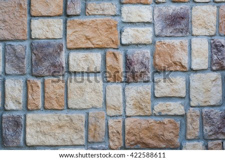 wall built of rectangular stones of different colors and textures - stock photo
