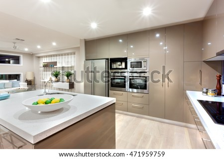 Wall cabinets with the ovens and the refrigerator in front of the white counter top with fruit dish and faucet next to the black stove illuminated using lights, there is a living room