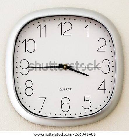 Wall Clock in an office marking a quarter to four, getting close to the time of leaving - stock photo