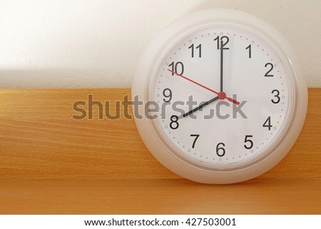 Wall clock on a wood background show the 8 o'clock - stock photo