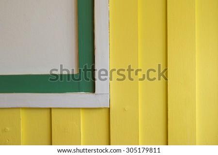 Wall detail. Corner white window on yellow wood wall. - stock photo