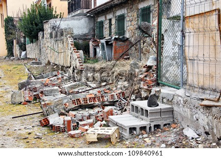 Wall dilapidated house with a cat watching - stock photo