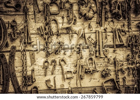 Wall Filled with Old Rusty Tools Hanging on the wall - stock photo